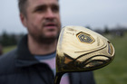 A man holds a golf club with the name of Ukrainian President Viktor Yanukovich on a golf course at the Ukrainian President Yanukovych's countryside residence. Photo / AP