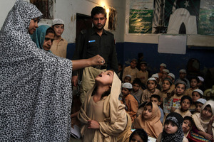A Pakistani health worker vaccinates a schoolgirl against polio, in Pakistan, where there are still outbreaks of the disease. Photo / AP