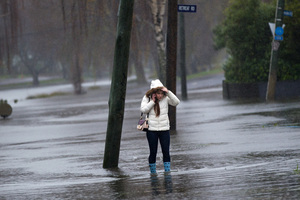 A young woman walks along a flooded Avonside Drive. File photo / Martin Hunter