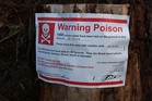 Warnings of 1080 poisoning are a familiar sight in bush and forests and many people complain of the risk to dogs. Photo / AP