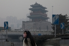 A woman wears a mask to combat Bejing's smoggy streets. Photo / AP