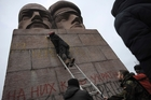 Protesters paint on the KGB officers monument in Kiev. Photo / AP