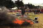 Revellers at the BW Festival watch as a young man leaps over a burning tent. Photo / Supplied