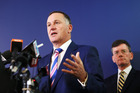 John Key speaks to the media last year as Security and Intelligence Minister Christopher Finlayson looks on.
