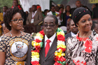 Zimbabwes President Robert Mugabe,flanked by his daughter Bona, left, and wife Grace during celebrations to mark his 91st birthday in the resort town of Victoria Falls, Zimbabwe. Photo / AP