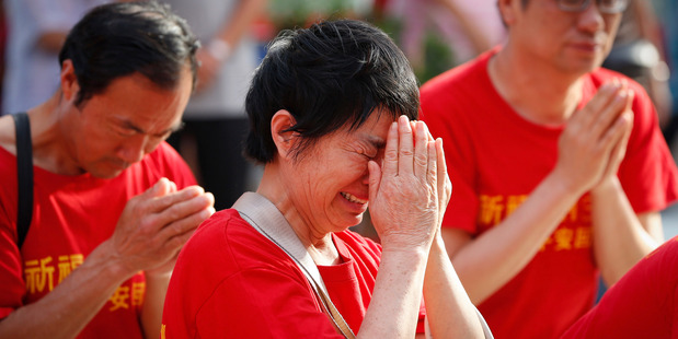 Distraught Chinese family members of MH370 passengers pray at a temple in Kuala Lumpur, Malaysia, on March 1, 2015. Photo / AP