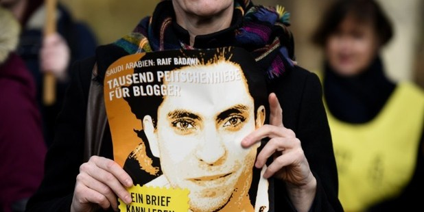 An Amnesty International activist holding a picture of Saudi blogger Raif Badawi during a protest against his flogging punishment. Photo / AP