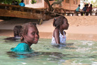 Local kids swim in the warm waters near Saeragi. Photo / Richard Moore