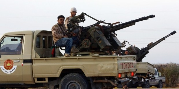 Members of a brigade loyal to the Fajr Libya (Libya Dawn), an alliance of Islamist-backed militias, sit on a pick up truck mounted with a machine gun. Photo / AFP