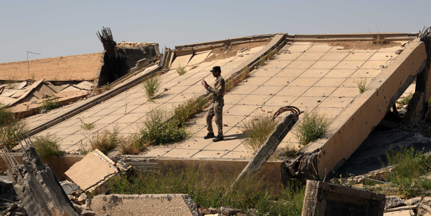 An Iraqi soldier takes photos of the demolished tomb. Photo / AP