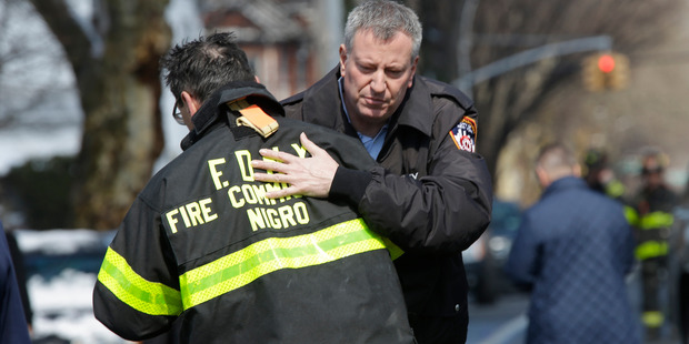 New York City Mayor Bill de Blasio hugs Fire Commissioner Daniel Nigro as he arrives at the scene of a fatal fire in the Brooklyn borough of New York. Photo / AP
