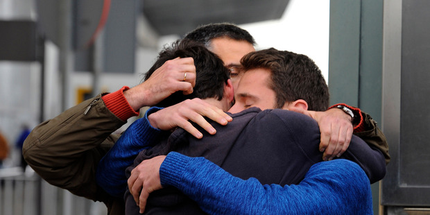 People comfort each other as they arrive at the Barcelona airport in Spain. Photo / AP