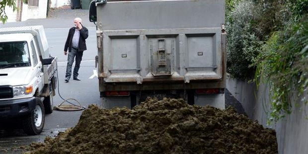Contractors prepare to clean up excrement dumped outside the Otago Regional Council's Dunedin office by a disgruntled North Otago farming couple. Photo / Peter McIntosh