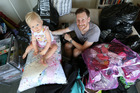 Greg and his daughter Tallulah, 17 months, with the piles of stuff awaiting disposal. Photo / Fiona Goodall