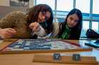 Eliana Rosenthal, left, and Lucy Levenson play scrabble in a club at school.  Photo / Getty