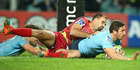 Brendan McKibbin of the Waratahs dives over to score a try as he is tackled by Nick Frisby of the Reds in their Super Rugby clash last night. Photo / Getty Images