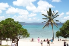 Travellers and locals mingle on one of Lifou's idyllic beaches. Photo / 123RF