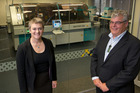 Maria Robertson and David Philp with the passport personalisation system in their Logistical Support Centre in Wellington. Photo / Mark Mitchell, NZ Herald