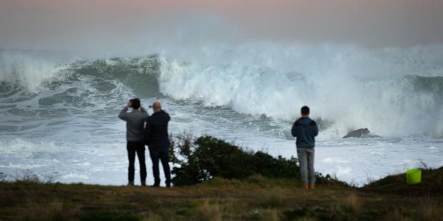 Sightseers watch huge ocean swells between Owhiro Bay and Island Bay, Wellington, last month. Photo / Mark Mitchell