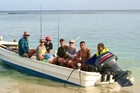 The writer (third from right next to a shirtless Charles Piutau) and his buddies had to amuse themselves fishing. Photo / James Russell