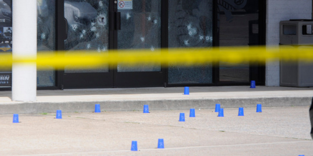 Bullet holes can be seen in the windows of the Armed Forces Recruitment Center. Photo / AP