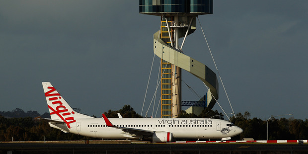 A Virgin Australia Boeing 737 touches down in front of the air traffic control tower at Sydney Airport. Photo / Bloomberg