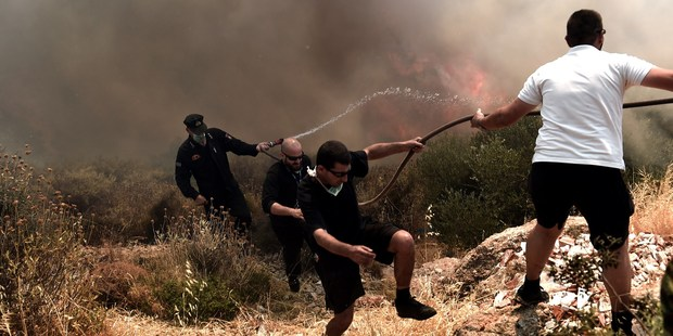 People and firefighters run away from a fire progressing in Athens on July 17, 2015. Photo / Anadolu Agency