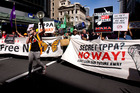 Protesters march down Queen St in opposition to the government's proposed TPP trade deal. Photo / Dean Purcell