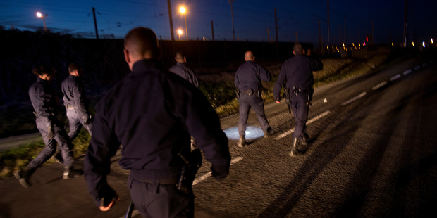 Police officers patrol as they look for migrants attempting to access the Channel Tunnel in Calais, northern France. Photo / AP