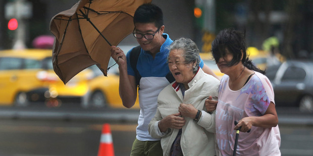 An elderly woman is escorted in the strong winds from Typhoon Soudelor in Taipei, Taiwan. Photo / AP