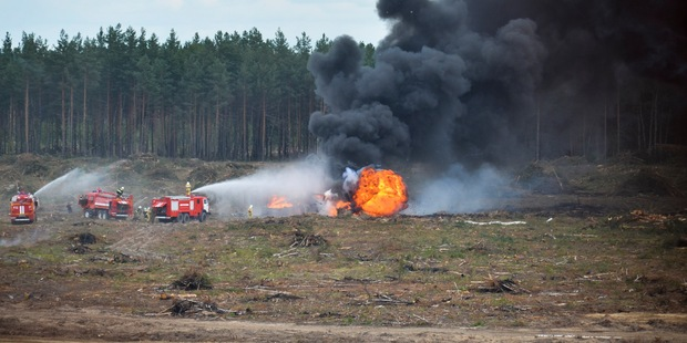 Firefighters extinguish a burning Russian military helicopter after it crashed during an aerobatic display in Dubrovichi, Russia. Photo / AP