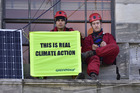 Greenpeace activist are seen with signs saying 'This is Real Climate Change' at Parliament House. Photo / Marty Melville, Getty Images