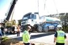 A 60-tonne crane from Palmerston North hoists the crippled milk tanker from the side of SH2 after the unladen vehicle was involved in a high speed head-on collision with a car.