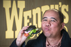 Reporter Lincoln Tan taste tests the new Black Gourmet Kiwi Classic Burger from Wendy's. Photo / Greg Bowker