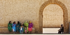 Locals sit in the shade of the city walls of Essaouira. Photo / Shutterstock