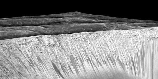Dark narrow streaks called recurring slope lineae emanate out of the walls of Garni crater on Mars. Photo: Nasa/AFP/Getty Images
