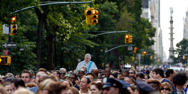 A cardboard cutout of Pope Francis is visible over the crowd waiting to watch a papal procession in New York. AP photo / Adam Hunger