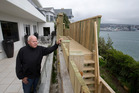 Peter Aitchison and the four-metre-high wooden fence blocking the view of Wellington City and Harbour from his apartment in Roseneath. Photo / Mark Mitchell