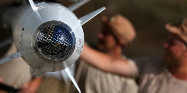 Russian military support crew inspect missiles attached to a jet at an air base in Syria. Photo / AP