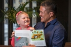 Cancer patient Kate Diprose shows off her book illustrations with All Black  Keven Mealamu.   Photo / Greg Bowker