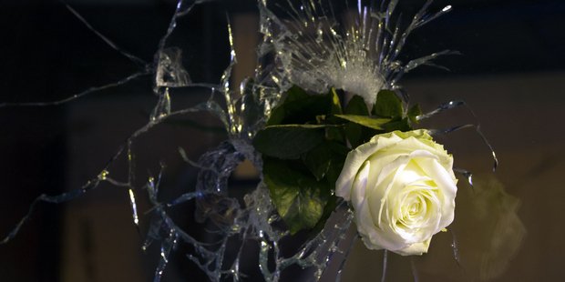 A rose is pictured in a bullet hole in a window, rue de Charonne, in Paris. Photo / Getty Images