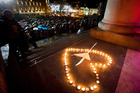 Candles are placed in the shape of a heart outside the Vancouver Art Gallery as hundreds of people gather to honor the victims of the deadly Paris attacks. Photo / AP