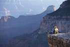 A couple take up a highly precarious position to enjoy the view of the Grand Canyon's North Rim. Photo / Mark Meredith