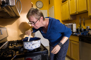 Cheryl Douglass smells for a whiff of the garlic flavour while preparing scalloped potatoes for her family's Thanksgiving dinner at her home. Photo: Nikki Kahn / Washington Post