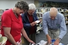 Ann Berry, of Pongaroa, and Pat Mills and Mark Redward, of Dannevirke, poring over copies of the newly minted book and archival photos.