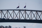 Flags at half mast on top of the Auckland Harbour Bridge. Photo / Dean Purcell