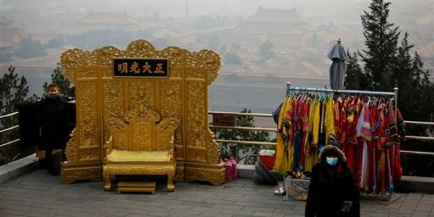 A vendor wearing a protective face mask waits for customer at the Jingshan Park. Photo / AP