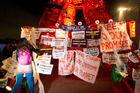 A participant puts posters on the mini red Eiffel Tower as NGO representatives staged a sit-in protest to denounce the first draft COP21 Climate Conference agreement. AP photo / Francois Mori