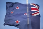 The New Zealand flag flutters outside outside the New Zealand Post building in Wellington. Photo / Getty Images