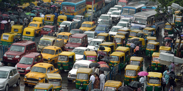 Indian commuters cross the road amid heavy rush hour traffic in Kolkata. Photo / Getty